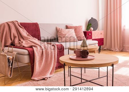 Two Coffee Cups On Wooden Coffee Table Next To Classy Grey Settee With Pastel Pink Pillows And Burgu