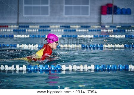 Female Athlete In A Red-yellow Swimsuit Is Swimming In The Style Of Breaststroke. Splashes Of Water