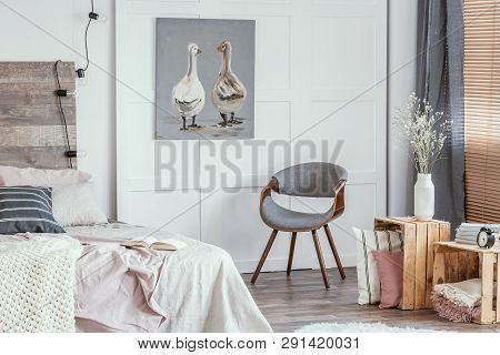 Delightful Bedroom Interior With Stylish Grey Chair, Wooden Boxes With Pillows And Blanket And King