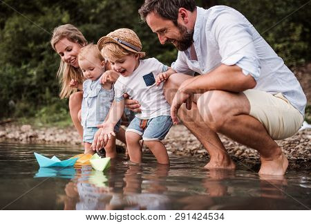 Young Family With Two Toddler Children Outdoors By The River In Summer, Playing.