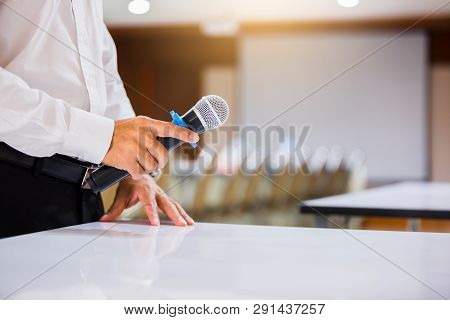 The Speaker Held The Microphone In His Hand With Blurry Conference Room And Projector