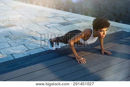 Fit african girl doing pushup exercise outdoor in the city street at dusk. Brazilian fitness woman working on abdominal muscles and triceps. Sporty young woman doing push ups exercises.