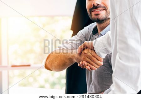 Close-up Of Two Businessmen Shaking Hands Together In Indoor Office Environment - Business Greeting,