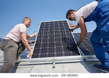 Male Workers Installing Stand-alone Solar Photovoltaic Panel System. Two Electricians Mounting Blue