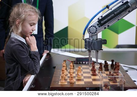 ST. PETERSBURG, RUSSIA - DECEMBER 27, 2018: Robot playing chess with a girl in Exhibition Hall Manege during World Rapid and Blitz Chess Championship 2018. The robot simultaneously plays on 3 boards