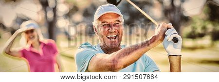 Portrait of happy mature golfer holding golf club while standing on field
