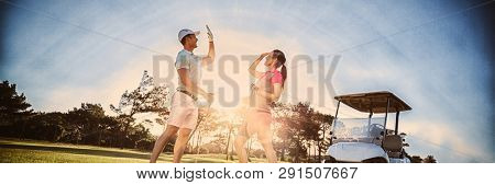 Full length of golf player couple giving high five while standing on field