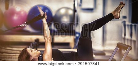 Woman practicing stretching exercise on reformer in gym