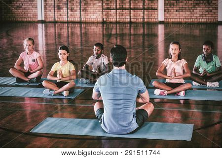 School kids and teacher meditating during yoga class in basketball court at school gym