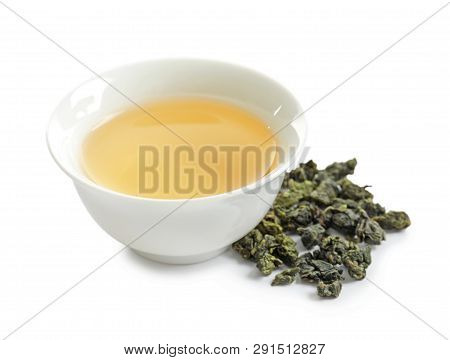Cup Of Tie Guan Yin Oolong And Tea Leaves On White Background