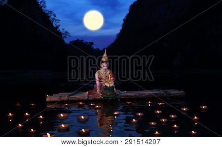 Beautiful Woman Wearing Thai Traditional Dress Sit On Bamboo Raft For River Goddess Worship Ceremony