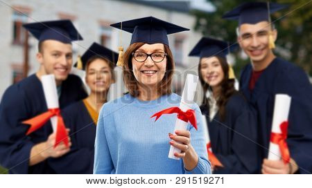 graduation, education and old age concept - happy senior graduate student woman in mortar board with diploma next to young people over university campus background