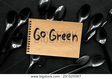 Go Green. Eco Concept And Injunction On The Use Of Plastic Flatware On Black Background Top View