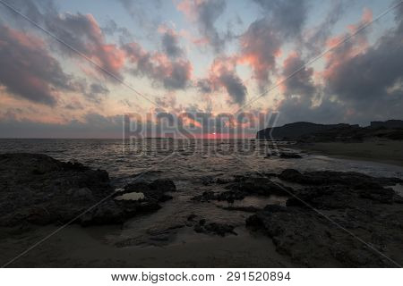 Pink and blue sunset on the beach in Creta, Greece. Beach with blacks rocks and waves at dusk poster