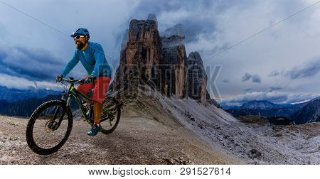Cycling man riding on bike in Dolomites mountains landscape. Cycling MTB enduro trail track. Outdoor sport activity.