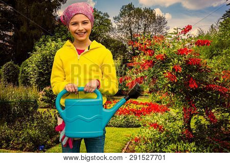 Playfull girl watering flowers with can in the garden at summer day. Child using watering can on sunny day. Little gardener playing in garden.