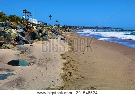 March 20, 2019 In Malibu, Ca:  People Walking On The Sandy Beach Besides A Neighborhood Of Homes Tak