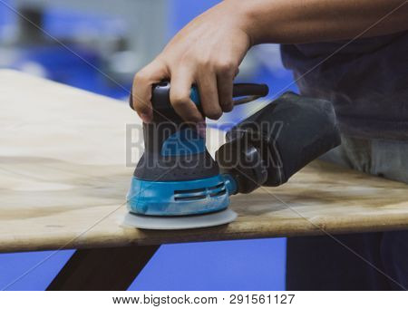 Carpenter using sander for wood table surface poster