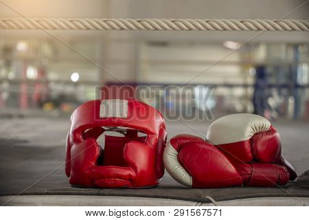 Boxing Headquard And Leather Mitt Glove Placed On Canvas Of Ring In Camp Of Training Boxer.equipment