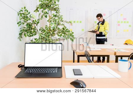 Professional worker writing while standing in conference room with laptop on foreground
