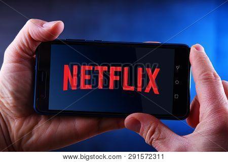 Poznan, Pol - Mar 24, 2019: Hands Holding Smartphone Displaying Logo Of Netflix, An American Media-s