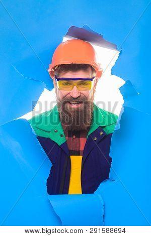 Mechanical Worker Looking Through Hole In Blue Paper. Industrial Worker. Man Builder In Hard Hat Mak