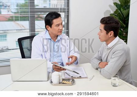 Asian Doctor Consults Young Patient. Worried Patient With His Doctor In Medical Office