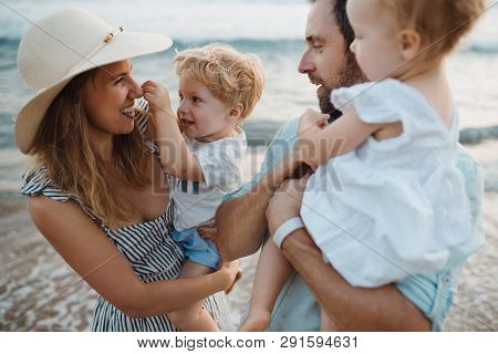 A Young Family With Two Toddler Children Standing On Beach On Summer Holiday.