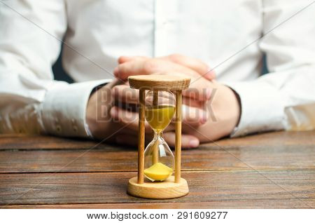 An Hourglass And Businessman Holds His Hands In The Lock. Job Interview Concept. Business Planning.