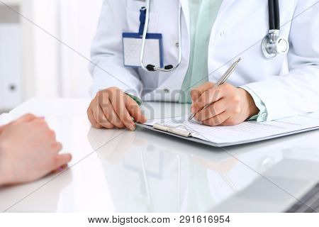 Unknown Doctor Woman Consulting Patient While Filling Up An Application Form At The Desk In Hospital
