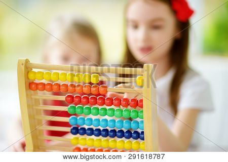 Two Cute Little Girls Playing With Abacus At Home. Big Sister Teaching Her Sibling To Count. Smart C
