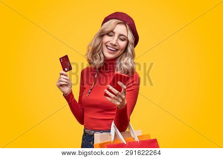 Excited Female With Red Plastic Card And Bunch Of Colorful Paper Bags Browsing Modern Smartphone Whi