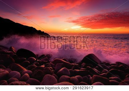 Purple Tinted Waves Breaking On A Rocky Beach At Sunset Over Porth Nanven In The Cot Valley Of Cornw