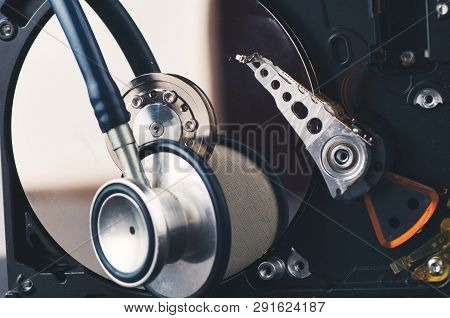 Technology And Data Recovery Concept, Stethoscope On Old Dusty Disassembled Hard Drive From The Comp