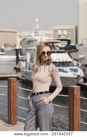 Stylish Female Standing Near Luxury Yacht At Pier Or Marina Promenade. Young Woman With Long Bob Hai