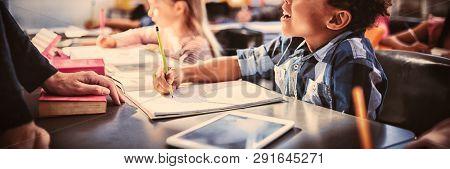 Teacher interacting with schoolboy in classroom at school