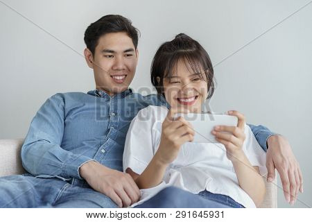 Happy Young Love Asian Couple Sitting On A Couch At Home, Looking At Mobile Phone, Asian Teen Couple