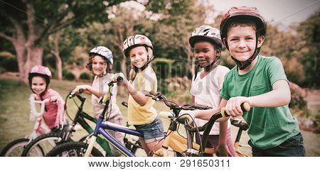 Smiling children posing with bikes in the park