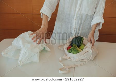 Female Hands Using Eco Natural Reusable Cotton Tote Shopper Bag Instead Of A Plastic Bag. Concept Of