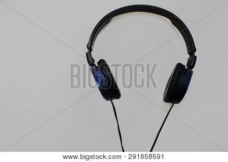 Black Headphones Isolated On Grey Empty Background. Music Listening Device Top View Image Of Modern