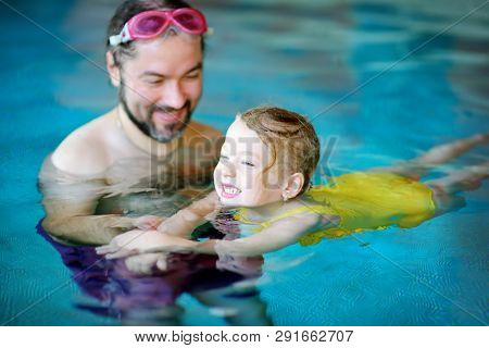 Happy Father Teaching His Little Daughter To Swim. Active Happy Child Learning To Swim.