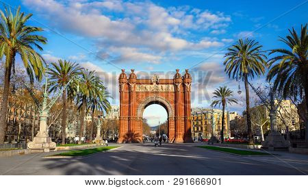 Triumphal Arch in Barcelona, Catalonia, Spain. Arc de Triomf at boulevard street. Alley with tropical palm trees. Early morning landscape with shadows and blue sky with clouds. Famous landmark. poster