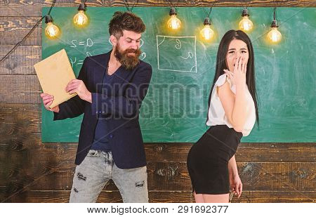 Man With Beard Slapping Sexy Student, Chalkboard On Background. Schoolmaster Punishes Sexy Student W