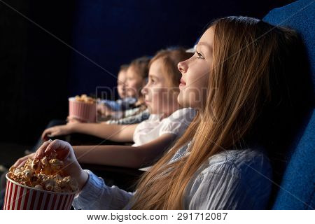Kids Sitting In Comfortable Chairs Of Movie Theatre, Watching Attentively Movie Or Cartoon. Beautifu