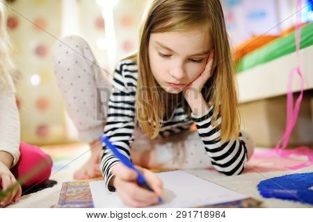 Two Cute Little Sisters Writing Letters Together At Home. Older Sister Helping Youngster With Her Ho