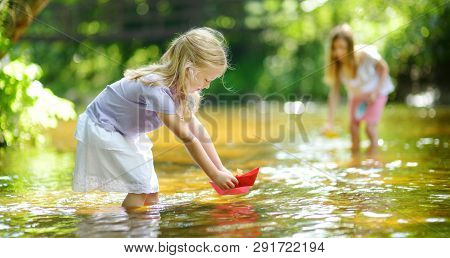 Two Little Sisters Playing With Paper Boats By A River On Warm And Sunny Summer Day. Children Having