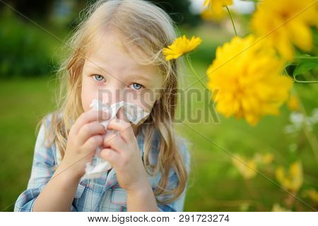 Cute Little Girl Blowing Her Nose By Beautiful Yellow Coneflowers On Summer Day. Allergy And Asthma