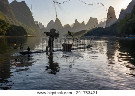 Silhouette Of Chinese Cormorant Fisherman Throwing A Fishing Net On A Lake In Guilin China.