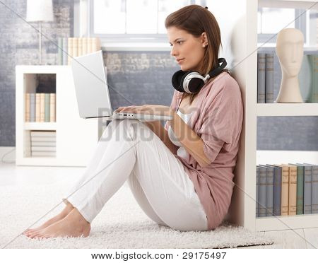 hübsche Frau mit Laptop-Computer und Kopfhörer, Eingabe, Blick auf Bildschirm, sitzen auf Wohnzimmer