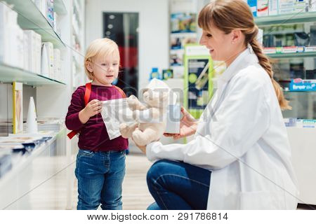 Pharmacist woman with child customer and her plush toy in pharmacy